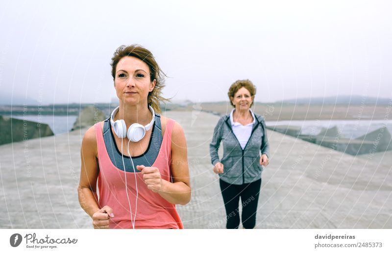 Young and senior sportswoman running by sea pier Lifestyle Wellness Ocean Sports Jogging Human being Woman Adults Mother Grandmother Fog Concrete Old Fitness
