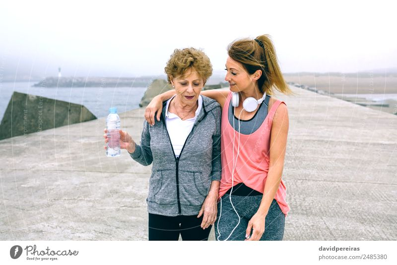 Two women walking by sea pier Bottle Lifestyle Leisure and hobbies Ocean Sports To talk Human being Woman Adults Mother Fog Old Fitness Athletic Authentic