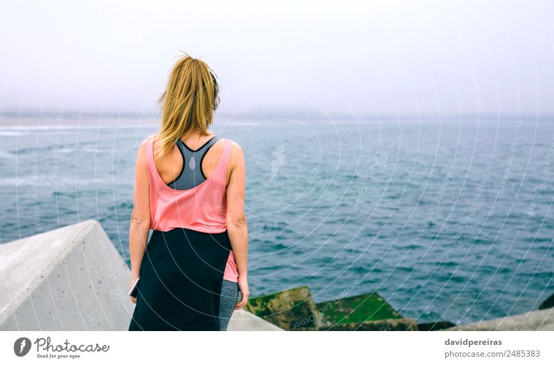 Unrecognizable young woman watching the sea Lifestyle Wellness Relaxation Calm Ocean Sports Telephone PDA Human being Woman Adults Fog Concrete Observe Fitness