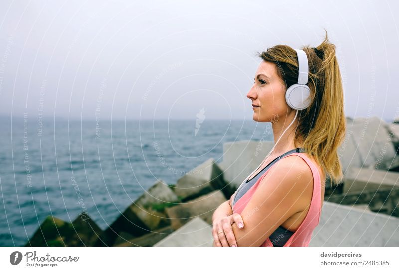 Sportswoman with headphones watching the sea Lifestyle Wellness Relaxation Calm Ocean Music Human being Woman Adults Fog Concrete Observe Think Fitness