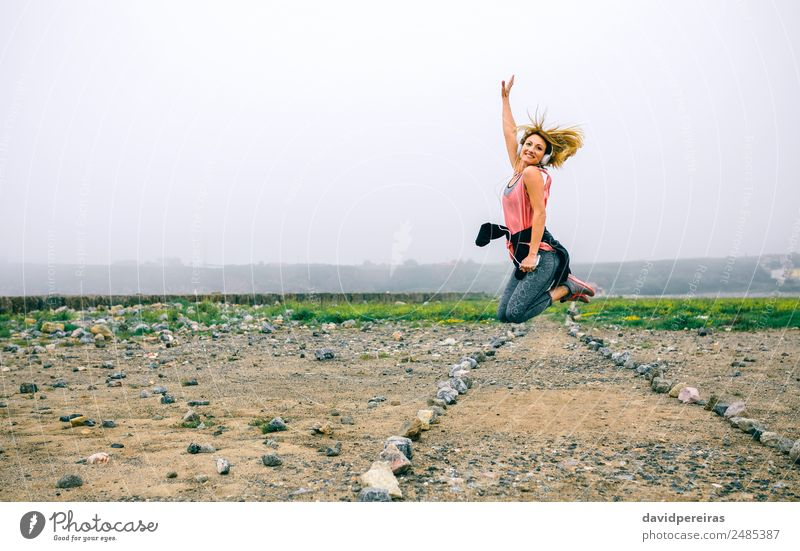 Young sportswoman jumping on the road Lifestyle Joy Happy Beautiful Music Sports Success Telephone PDA Human being Woman Adults Hand Landscape Fog Street