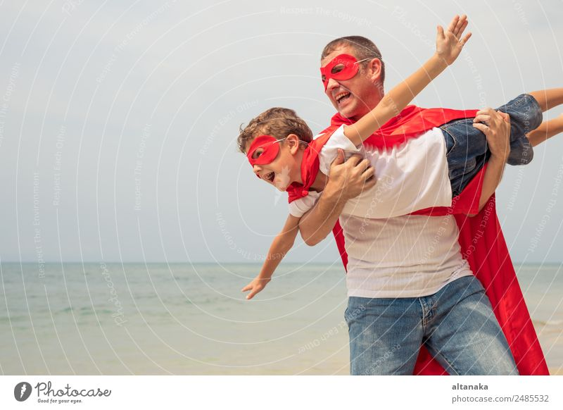 Father and son playing superhero on the beach at the day time. People having fun outdoors. Concept of summer vacation and friendly family. Lifestyle Joy Happy