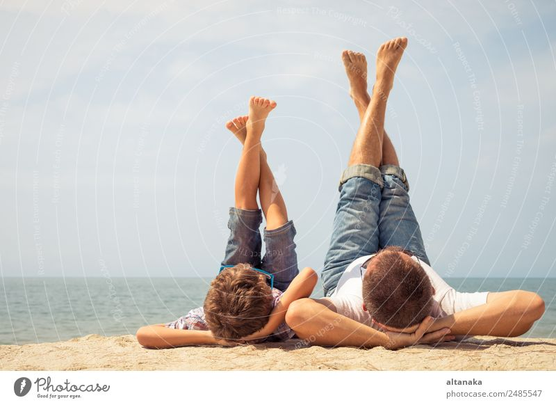 Father and son playing on the beach at the day time. People having fun outdoors. Concept of summer vacation and friendly family. Lifestyle Joy Happy Relaxation