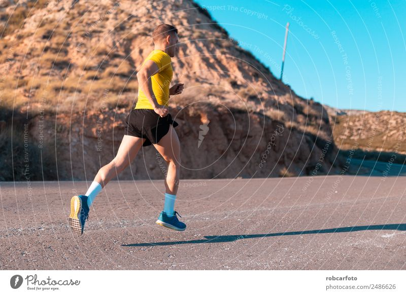 Young man running with greenish yellow shirt Lifestyle Sun Sports Jogging Human being Man Adults Park Bridge Movement Fitness Athletic Speed White young healthy
