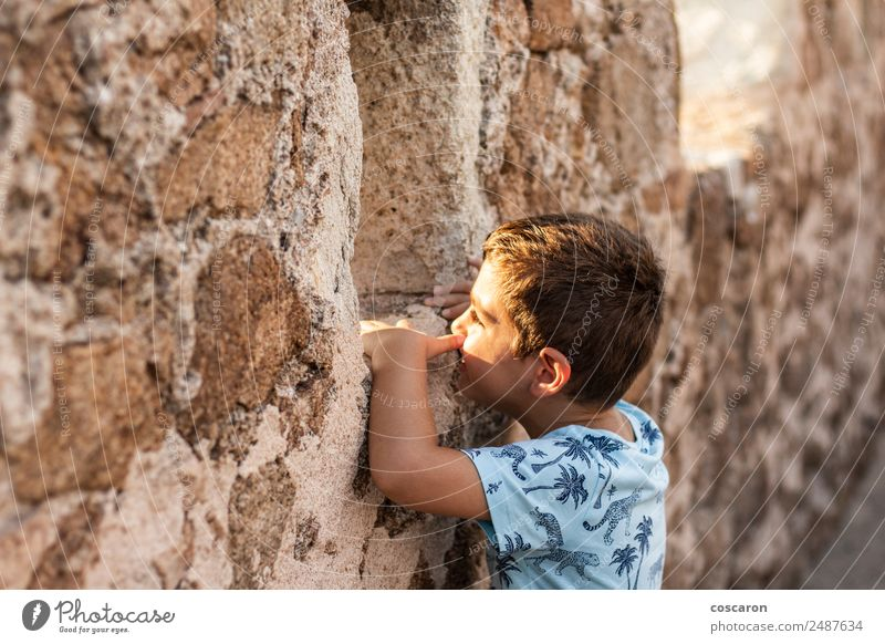 Little boy looking through the wall of a castle Child Human being Vacation & Travel Summer Lifestyle Wall (building) Boy (child) Tourism Wall (barrier) Trip
