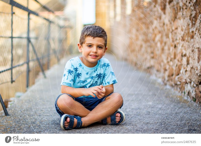Cute little boy seated on the wall of a castle Child Human being Vacation & Travel Blue Town Beautiful Architecture Lifestyle Wall (building) Happy Boy (child)