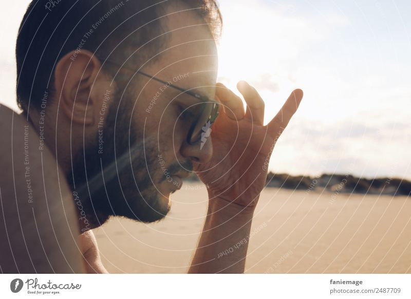 Ray of Light Human being Masculine Hair and hairstyles Face 1 Think Camargue Sunbathing Warmth Sand Beach Sunglasses Hand Gesture Relaxation Reading