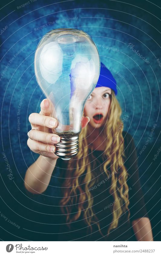 Young woman holding a huge light bulb Lifestyle Style Design Hair and hairstyles Leisure and hobbies Technology Science & Research Advancement Future