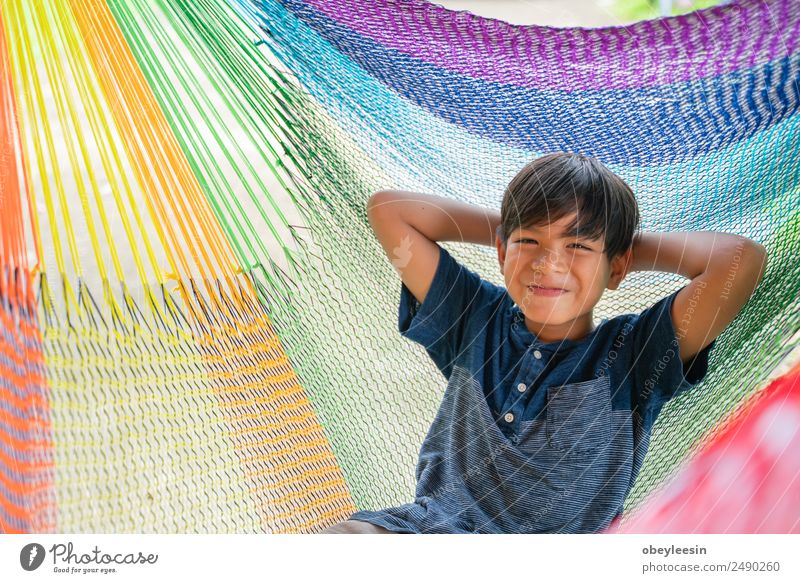 The little boy sitting at the hammock and he so happy Lifestyle Joy Happy Relaxation Leisure and hobbies Vacation & Travel Summer Garden Child Human being