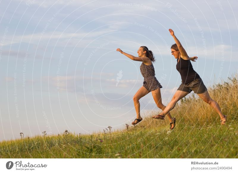 2 young women jump across the meadow Lifestyle Leisure and hobbies Human being Feminine Young woman Youth (Young adults) Brothers and sisters Sister Friendship