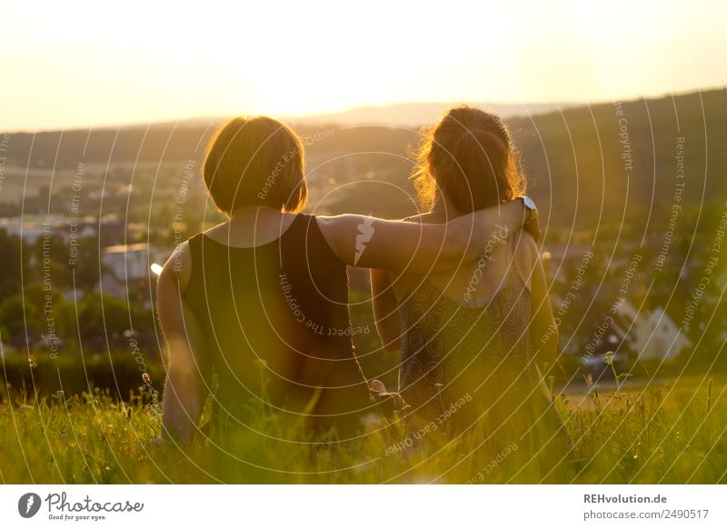 2 young women sitting on the meadow looking into the distance Leisure and hobbies Freedom Summer Human being Woman Adults Brothers and sisters Sister Friendship