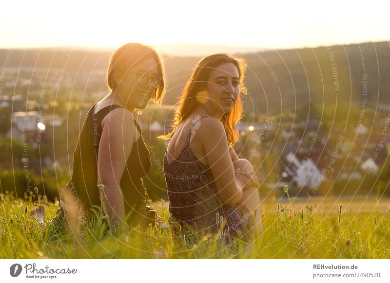 Two women sitting on a meadow in the evening light Lifestyle Human being Young woman Youth (Young adults) Woman Adults Brothers and sisters Sister Friendship 2