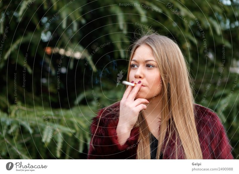 Pretty blond girl with long hair smoking Lifestyle Elegant Style Joy Happy Beautiful Face Make-up Human being Woman Adults Nature Grass Park Fashion Fur coat