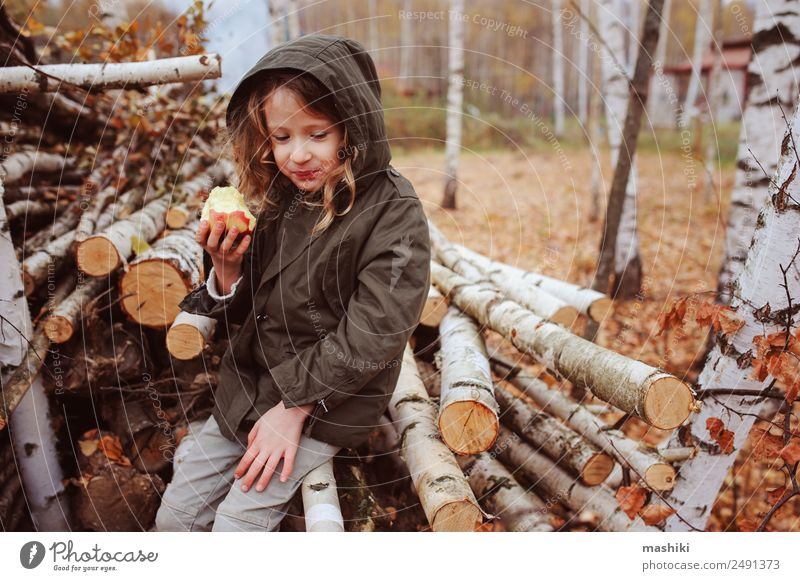 happy funny kid girl eating fresh apple in autumn Fruit Apple Lifestyle Joy Happy Playing Garden Child Infancy Nature Autumn Warmth Leaf Forest Scarf Smiling