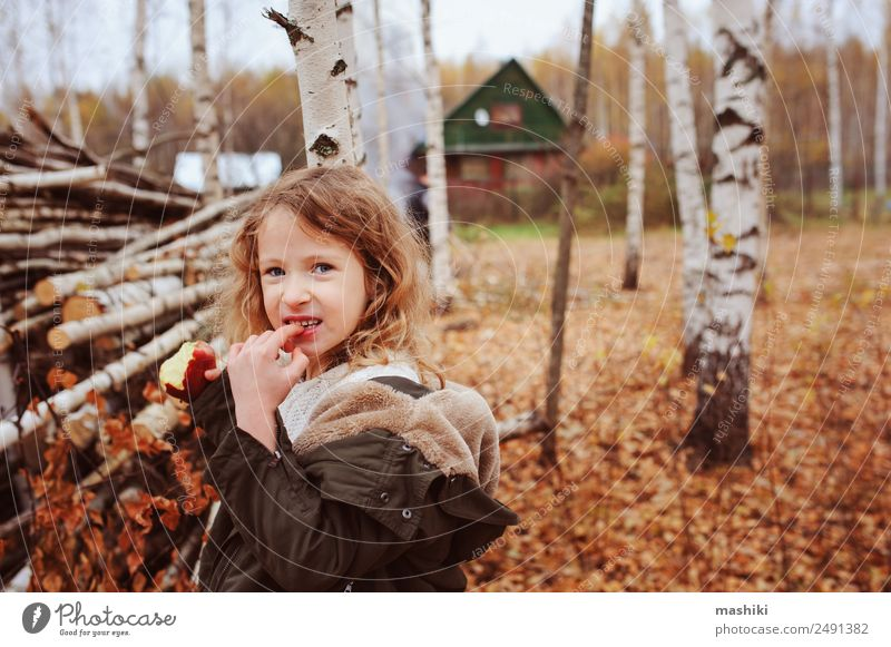 happy funny kid girl eating fresh apple in autumn Fruit Apple Lifestyle Joy Happy Playing Knit Garden Child Infancy Nature Autumn Warmth Leaf Forest Scarf