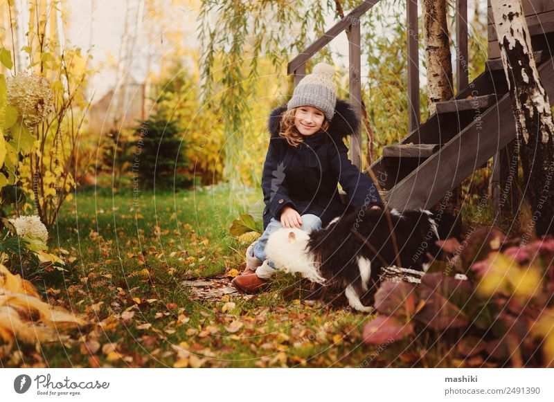 autumn portrait of happy kid girl playing with her dog Lifestyle Joy House (Residential Structure) Garden Child Friendship Nature Autumn Coat Hat Pet Dog Wood