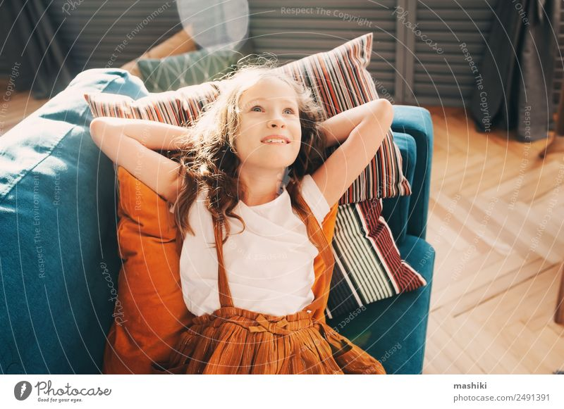 happy kid girl relaxing on cozy couch in modern living room. Lifestyle Happy Flat (apartment) House (Residential Structure) Moving (to change residence)