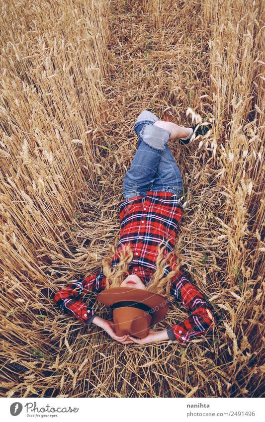 Young woman resting in a field of wheat Grain Organic produce Lifestyle Style Wellness Relaxation Leisure and hobbies Vacation & Travel Freedom Summer
