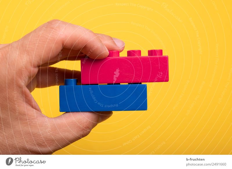 Two building blocks on top of each other Hand Fingers Plastic To hold on Blue Yellow Together Love Loyalty Contentment Brick Toys Offset In pairs Couple Match