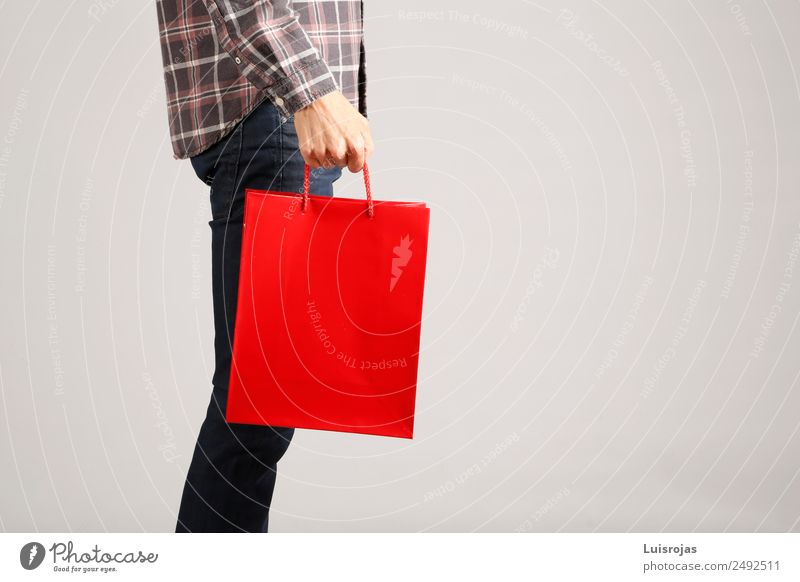 Man in jeans and plaid shirt with red bag in his hand Shopping Joy Valentine's Day Mother's Day Christmas & Advent Masculine Young man Youth (Young adults) Hand