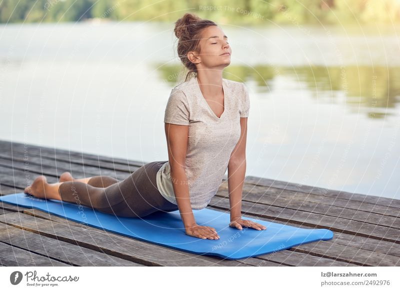 Attractive woman working out on a wooden deck Woman Human being Beautiful White Relaxation Adults Lifestyle Lake Copy Space Body Fitness Energy Wellness Posture