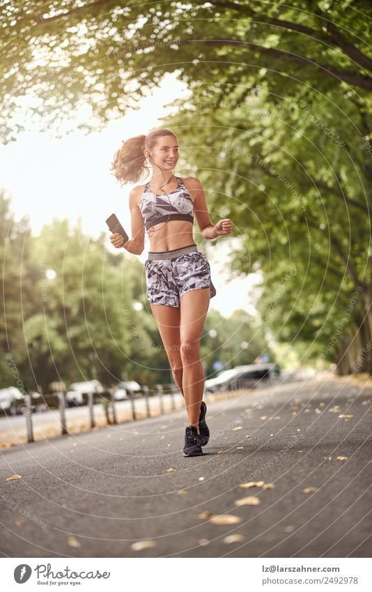 Happy fit woman jogging with her smart phone Lifestyle Summer Music Sports Jogging Telephone Woman Adults 1 Human being 18 - 30 years Youth (Young adults)