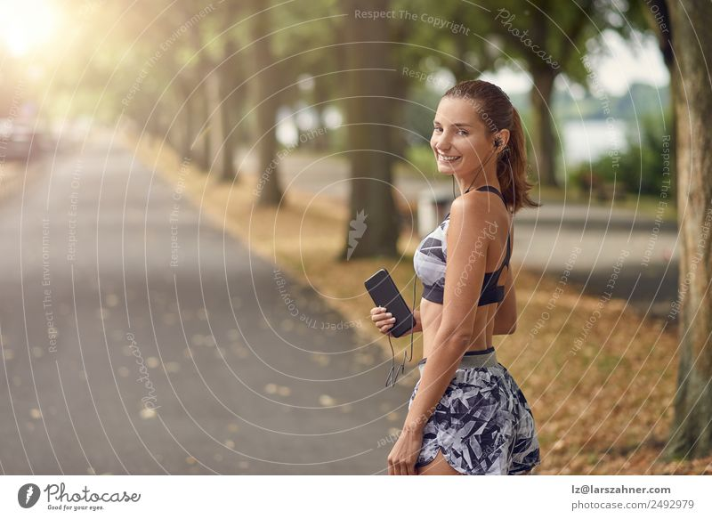 Attractive sporty woman with her mobile phone Lifestyle Body Face Summer Music Sports Jogging Telephone PDA Camera Woman Adults 1 Human being 18 - 30 years
