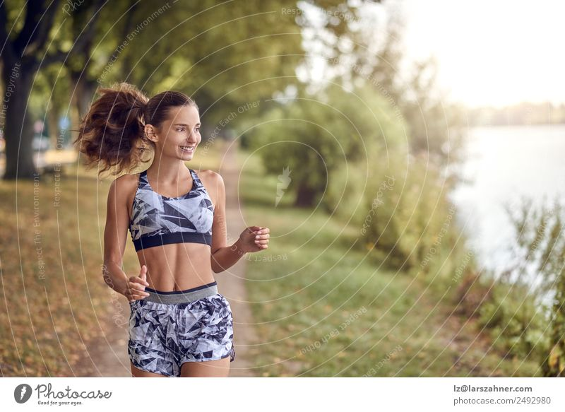 Fit healthy athletic woman jogging on a river bank Lifestyle Happy Summer Sports Jogging Woman Adults 1 Human being 18 - 30 years Youth (Young adults) Warmth