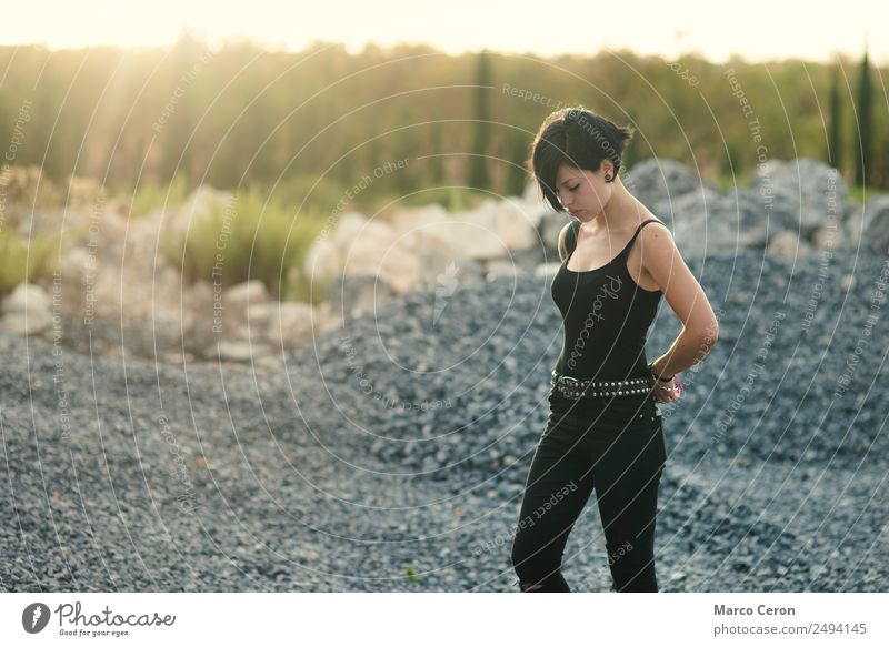 beautiful girl with short haircut and wearing black clothes in countryside enjoying the sunset attractive background breathing caucasian day dreaming fashion