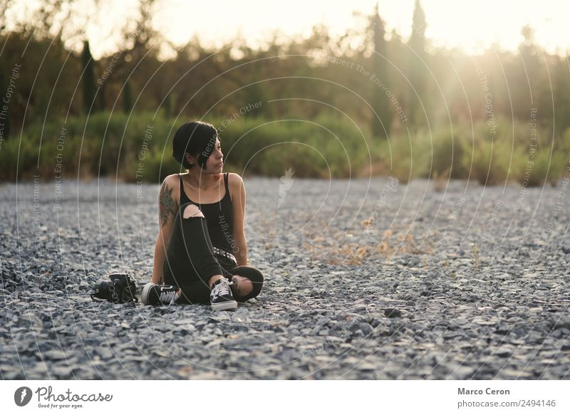 Beautiful photographer girl wearing black clothes sitting on stone floor in countryside with her camera attractive background backlight beautiful breathing