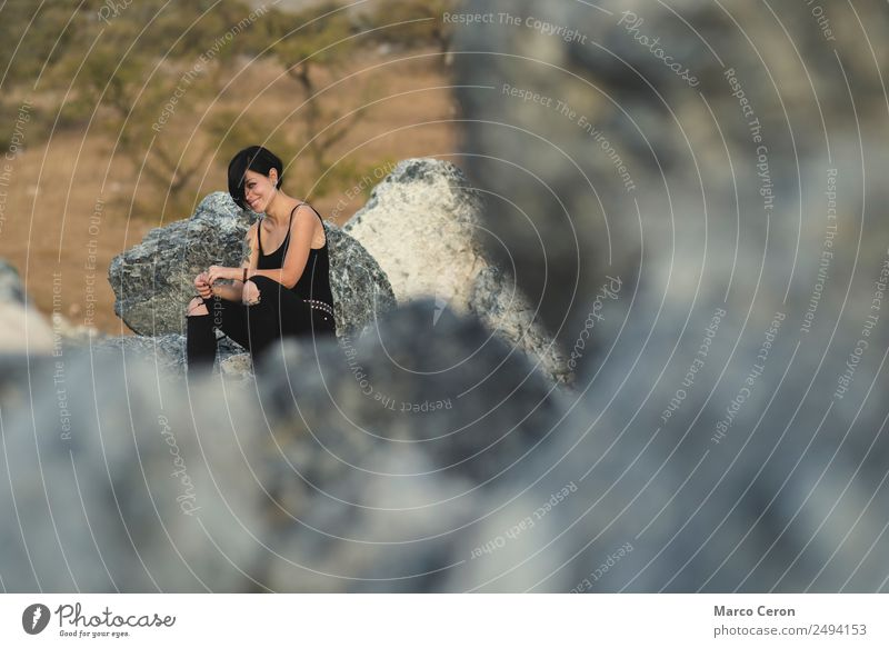 Beautiful young woman smiling sitting happy on the rocks outdoors in countryside attractive background beautiful black clothes brunette camera caucasian day