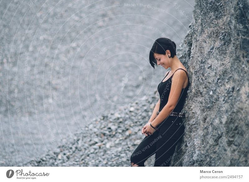 beautiful brunette short hair girl leaning on gray rock wall outdoors smiling happy attractive background black breathing caucasian day fashion female freedom