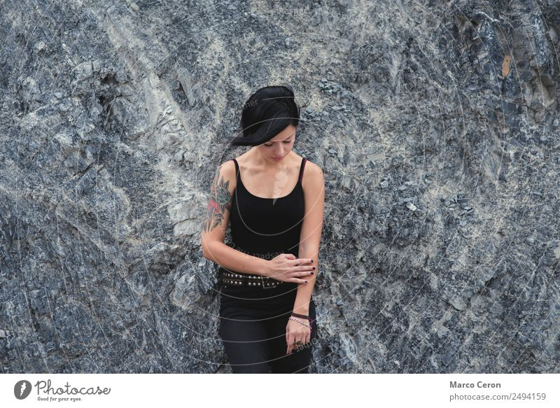 beautiful brunette short hair girl leaning against  gray rock wall outdoors, wearing black clothes attractive background black hair breathing caucasian day