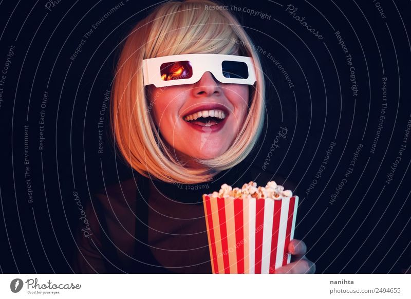 Young blonde woman enjoying a movie in the cinema Food Fast food Popcorn Lifestyle Style Joy Leisure and hobbies Event Going out Human being Feminine Young man