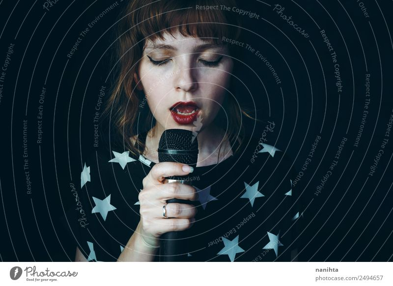 Young woman singing into the darkness Lifestyle Elegant Style Design Face Leisure and hobbies Party Event Music Feasts & Celebrations Technology Microphone