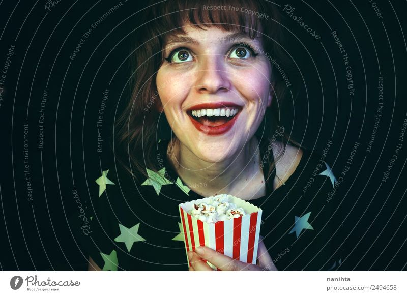 Cheerful young woman watching a movie Food Popcorn Lifestyle Style Wellness Leisure and hobbies Entertainment Going out Human being Feminine Young woman