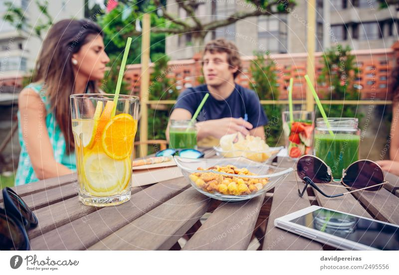 Infused fruit water cocktails and people talking in background Woman Nature Man Summer Green Adults To talk Natural Couple Friendship Fruit Leisure and hobbies