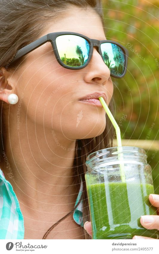 Woman with sunglasses drinking green vegetable smoothie outdoors Vegetable Fruit Nutrition Diet Beverage Juice Lifestyle Happy Beautiful Summer Garden
