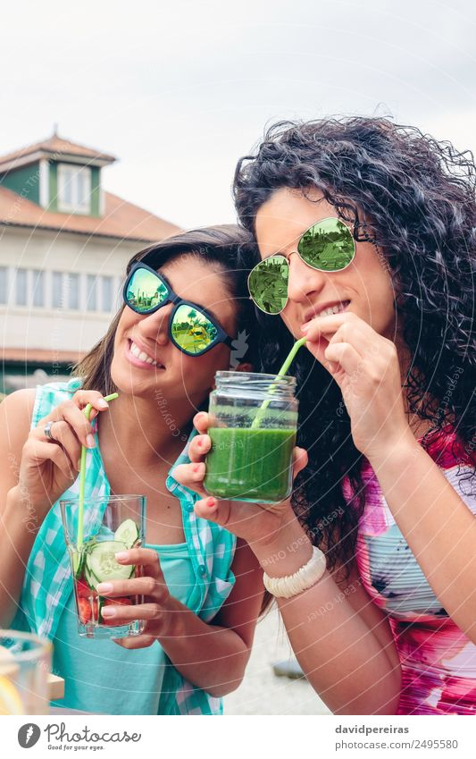 Two women with sunglasses drinking organic beverages outdoors Woman Human being Nature Summer Green Adults Lifestyle Natural Emotions Happy Fruit Nutrition
