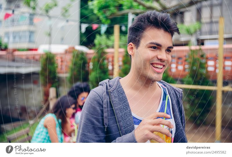 Young man holding glass of infused water cocktail outdoors Fruit Beverage Juice Lifestyle Joy Happy Leisure and hobbies Summer Garden Table Human being Woman