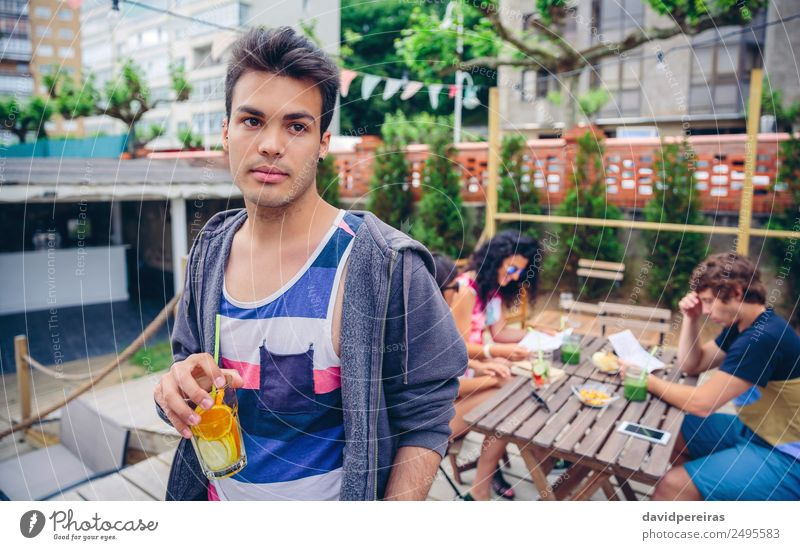 Young man drinking infused water cocktail outdoors Fruit Beverage Juice Lifestyle Joy Happy Leisure and hobbies Summer Garden Table Human being Woman Adults Man