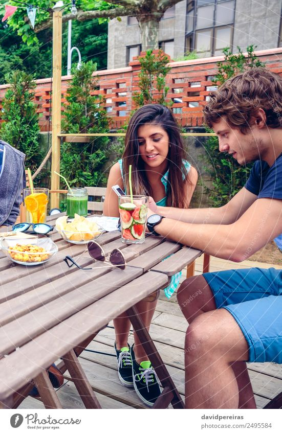 Young happy couple looking smartphone outdoors in summer Vegetable Fruit Beverage Lifestyle Joy Happy Leisure and hobbies Summer Garden Table Telephone PDA