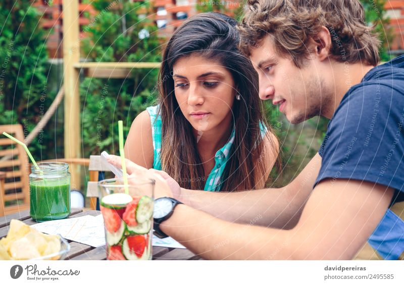 Young couple looking smartphone outdoors in summer Vegetable Fruit Beverage Lifestyle Joy Happy Leisure and hobbies Summer Garden Table Telephone PDA Technology