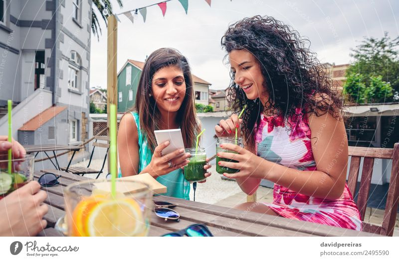 Two women looking smartphone and drinking green smoothies Woman Human being Nature Summer Green Adults Lifestyle Natural Emotions Happy Fruit Nutrition