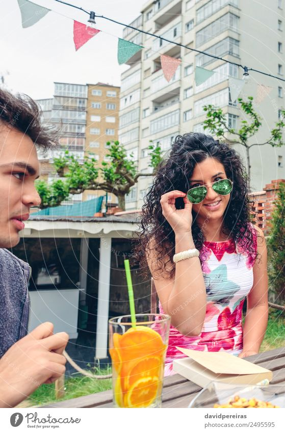 Smiling young woman looking at camera over sunglasses Fruit Beverage Tea Lifestyle Joy Happy Face Leisure and hobbies Summer Table Human being Woman Adults Man