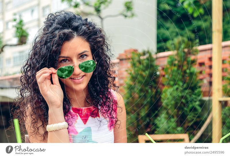 Smiling young woman looking at camera over sunglasses Woman Human being Summer Blue Beautiful Green Tree Relaxation Joy Face Adults Lifestyle Emotions Happy