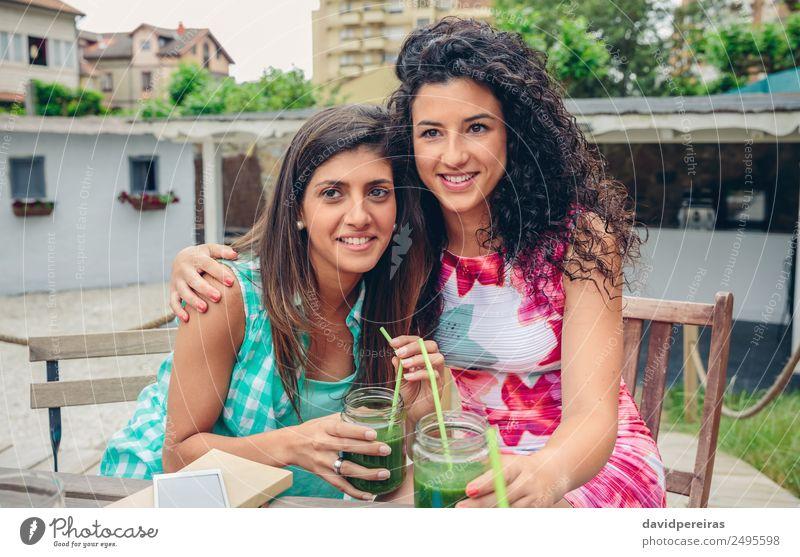 Two women embraced with smoothies looking at camera Vegetable Fruit Beverage Juice Lifestyle Joy Happy Leisure and hobbies Summer Human being Woman Adults