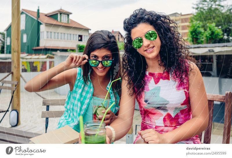 Two women with sunglasses and beverages looking at camera Vegetable Fruit Beverage Juice Lifestyle Joy Happy Leisure and hobbies Summer Human being Woman Adults