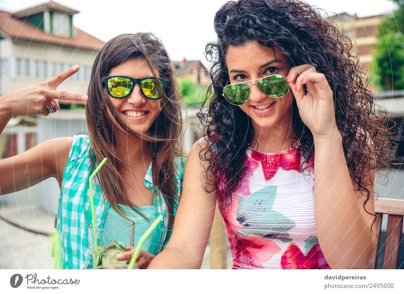 Two women with sunglasses and smoothies looking at camera Vegetable Fruit Beverage Juice Lifestyle Joy Happy Leisure and hobbies Summer Success Human being