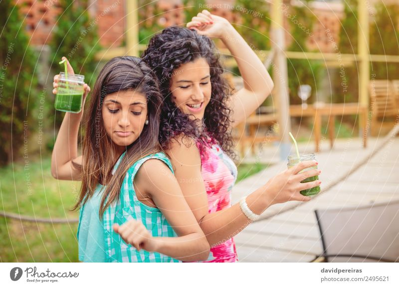 Young women couple with healthy drinks dancing outdoors Vegetable Fruit Beverage Alcoholic drinks Lifestyle Joy Happy Beautiful Leisure and hobbies